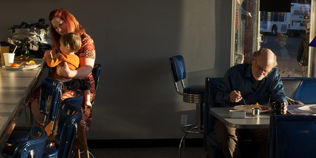 A photograph of a diner interior shows three figures lit by morning in a gray and blue room. At the left bar, a feminine figure with light skin cradles a small child in their lap. At the right table, an older masculine figure with light skin eats from a plate of food.