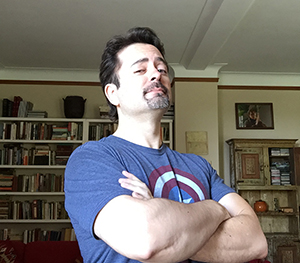A picture of Ben Zackheim in a blue Captain America t-shirt crossing his arms with bookshelves in the background.