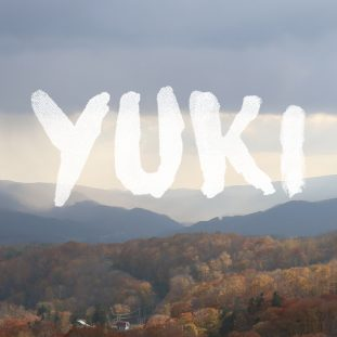 "Image of a mountain landscape with fall foliage, white text that reads ""YUKI"" on top."
