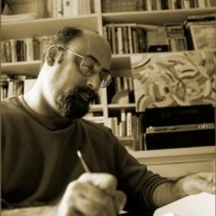 A sepia-toned photograph shows a bearded figure with glasses writing on paper. Behind the figure is a bookcase stacked with books and art.