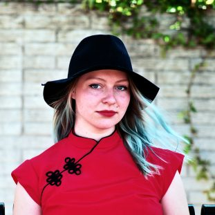 A white woman with ombre hair, a black hat, and a red Chinese style mandarin collar shirt.
