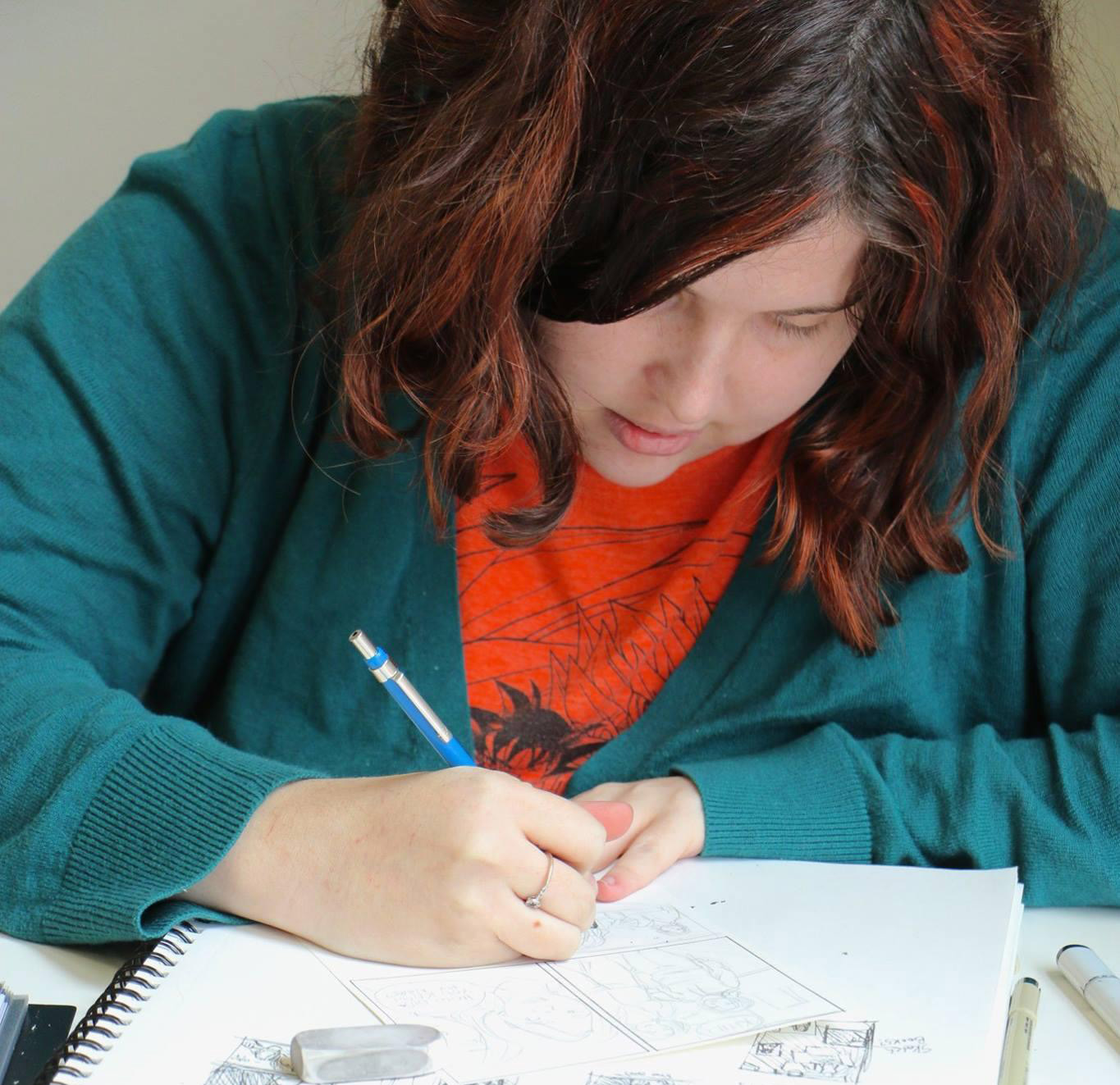 Photo of a white woman with brown hair, wearing a teal cardigan over an orange shirt, drawing.