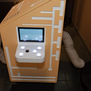 An orange podium with a game controller built into the side, white tech decoration patterns on the sides.