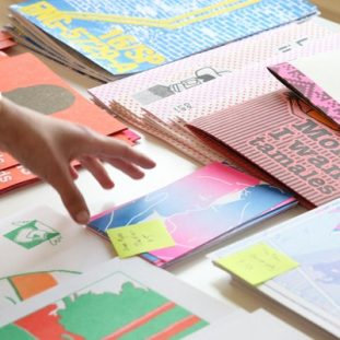 Photograph of a hand reaching towards a table full of riso printed zines and prints.