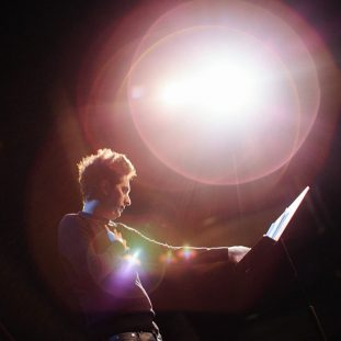 A figure with short hair and light skin reaches one hand to hold a music stand and spreads the other hand across their chest. Behind them are multiple circular lens flares in shades of red and purple.