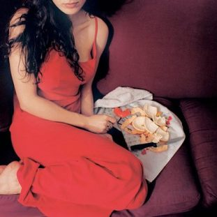 A photograph shows a feminine figure with light skin, long black hair, bare feet, and a red dress seated on a burgundy cough. The figure's face is cropped above their lips, and next to them is a plate with a kitchen knife and orange peels.