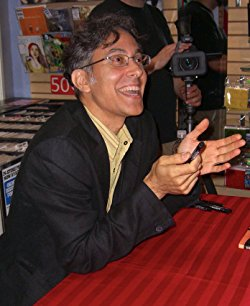 A photograph shows a seated figure with short black hair, glasses, and light skin widely smiling and gesturing. It appears the figure is conversing with another person out of frame.