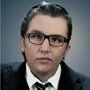 A white figure with glasses and a suit looks at the camera.