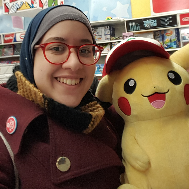 Photograph of Nada Mohammed posing with a stuffed Pikachu.