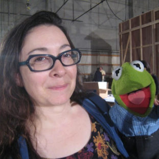 Headshot of Carol Silverman with a Kermit puppet.