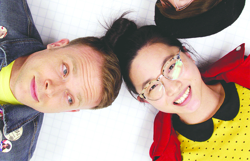 Photo of a white man in a denim jacket and an Asian woman with glasses, a yellow dress and red jacket with their heads pressed together.