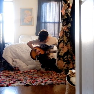 Photo of a figure playing guitar by a bed.