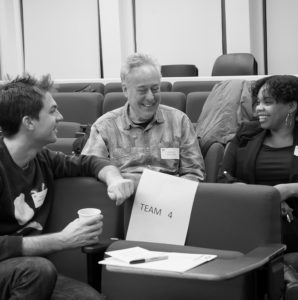 Black and white photo of three people smiling, sitting in tiered seats.