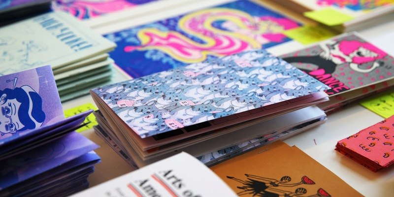 Photograph of a display of various small zines and prints.