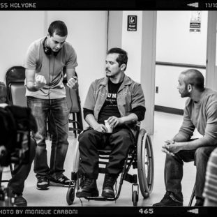 Black and white photograph of a group of various men sitting or standing in a circle with some equipment, the man in the center uses a wheelchair.