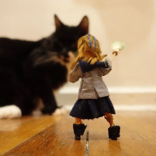 Photograph of a small sculpted figure with blonde hair, and a blue and gray grid jacket with their back to the viewer, holding a broom towards a real black and white cat.