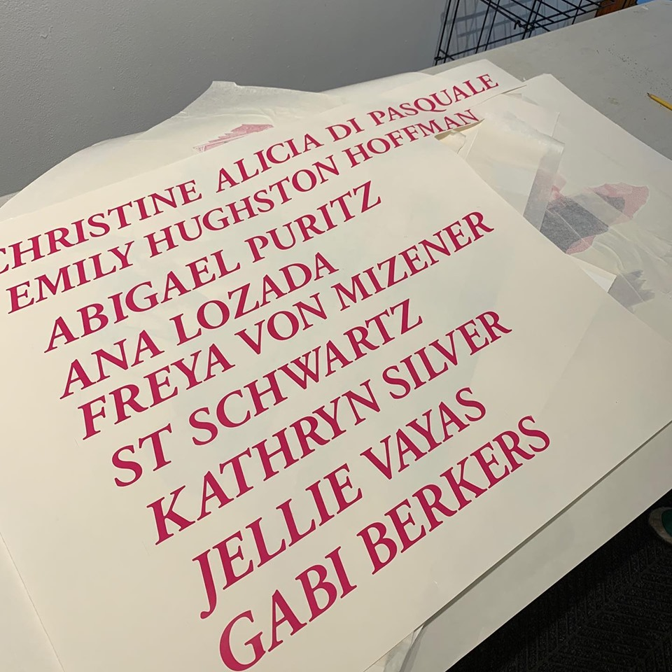 Photograph of offwhite paper with a large centered, all caps list of names in a red slab serif font.