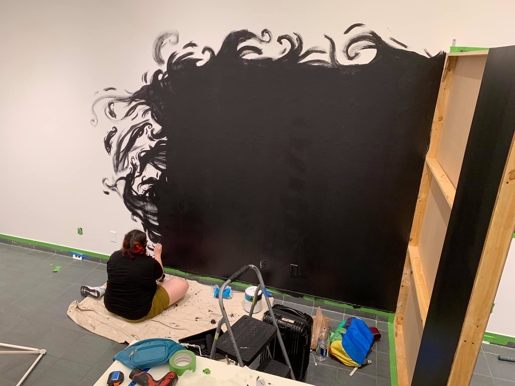 Image of a figure with dark hair with red streaks, painting a wall black with tendrils of black smoke extending from right to left into the unpainted, white side.