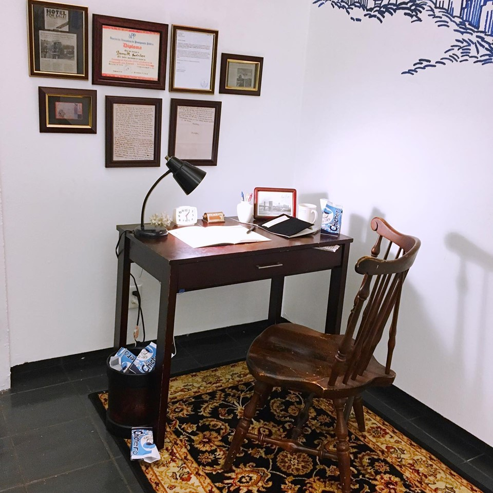 Photograph of a dark wood chair at a dark wood desk with some objects such as notebooks, a lamp, mugs and a photograph on it, framed writings are on the wall.