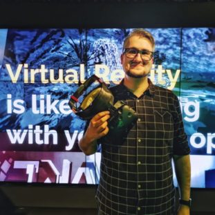 Sean Rodrigo holding a VR headset, standing in front of a screen display for VR.