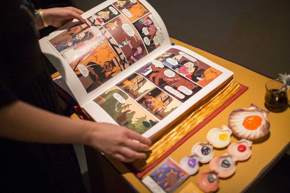 Photo by Bridget Badore, a display of shells with different colored paints in each one, next to light skinned hands holding an open comic book depicting characters with a large orange cat.