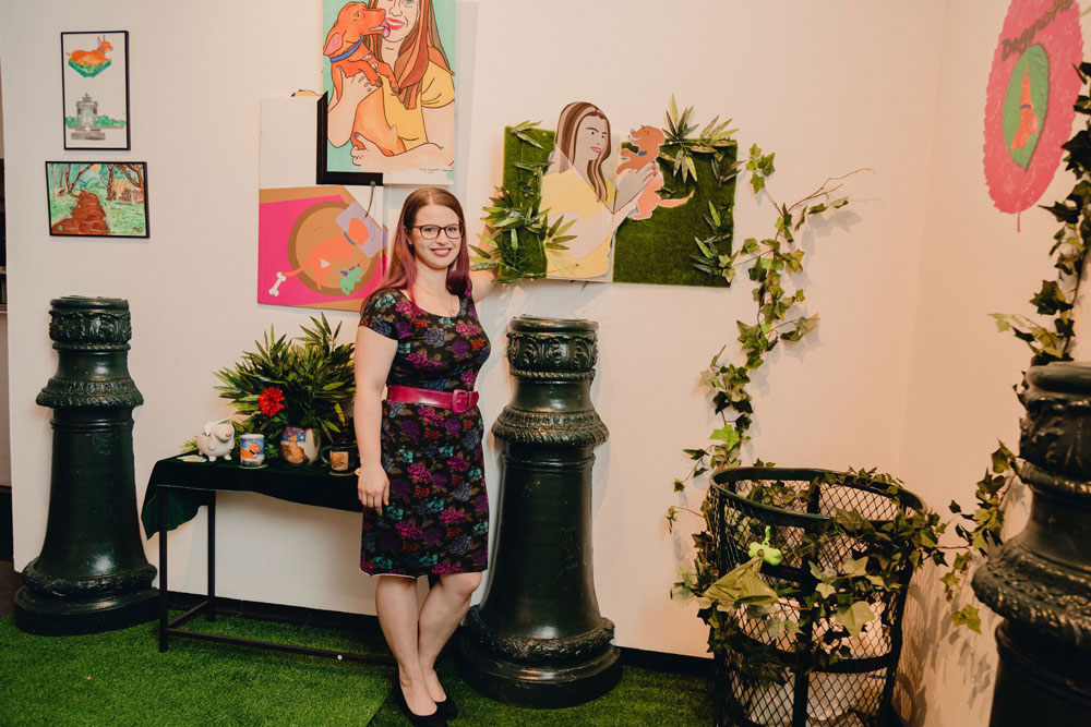 Photograph of a white woman with brown hair and glasses in a floral dress, standing next to a wall of paintings and installations of plants.