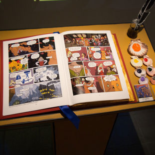 Photograph of an open comic book depicting characters with a large orange cat, displayed with different colored paints in shells.