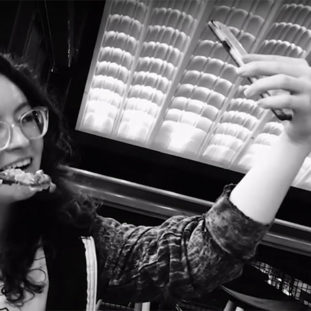 A black and white photo of a woman with curly dark hair, in glasses and a hoodie, eating and taking a selfie.