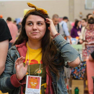 A white woman with a bandana, a denim jacket and long brown hair, wearing a lanyard for Cake 2015 exhibitors.