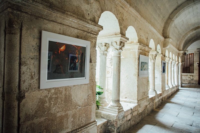 European style arched stone hall with arched windows and art pieces hanging in between the arches.