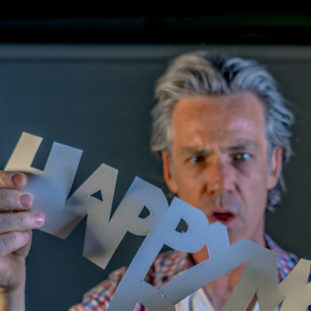 John Benton Artist & Storyteller headshot, he holds the cut out sign, 'happy'.