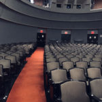 Empty seats in an auditorium with an orange walkway and three exits in the back.