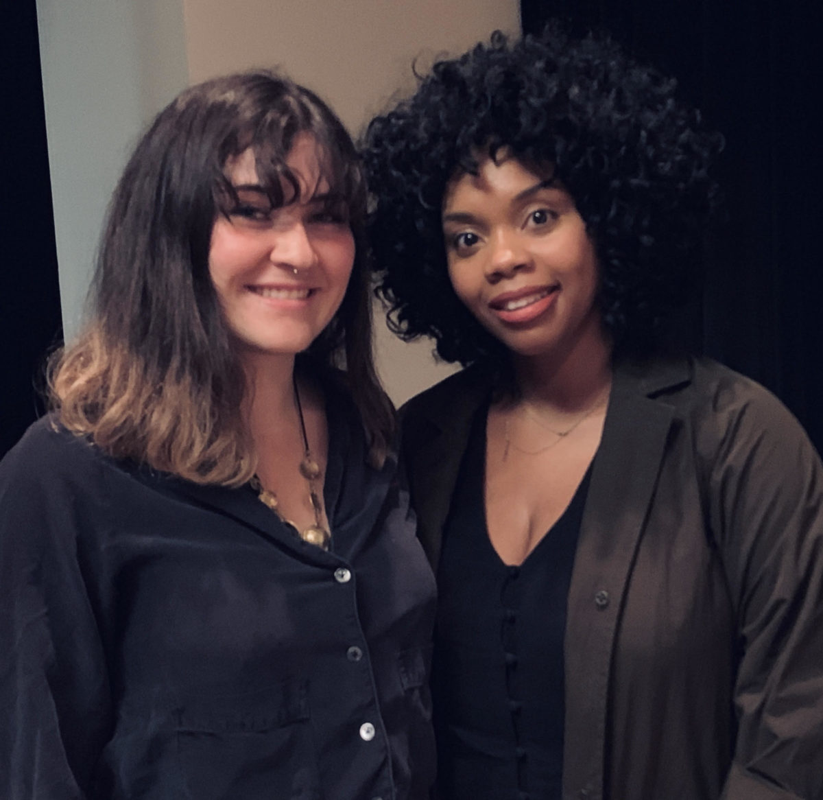 A white woman with brown hair and a black woman with natural hair stand next to each other smiling.
