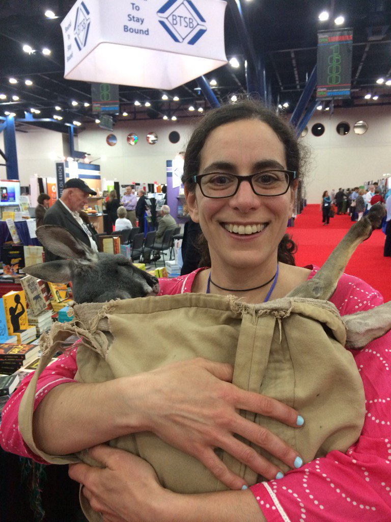 Sara Varon stands with a smile at a convention, holding a bag with a mammal with long ears inside of it.