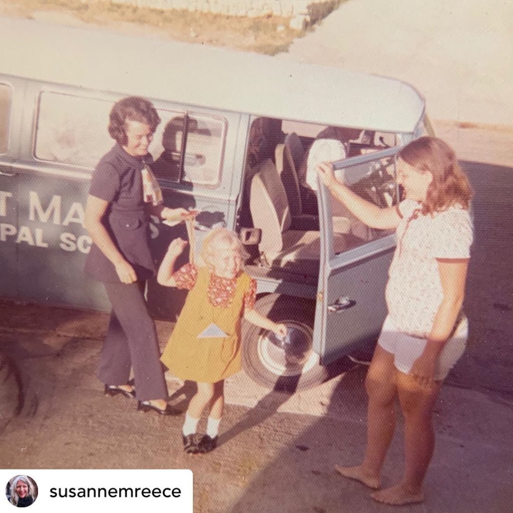 A photograph of three figures standing outside of a van. A white woman in black stands next to a small child with blonde hair in a yellow dress while another barefoot woman in a white t-shirt and shorts stands with her hand on the door.