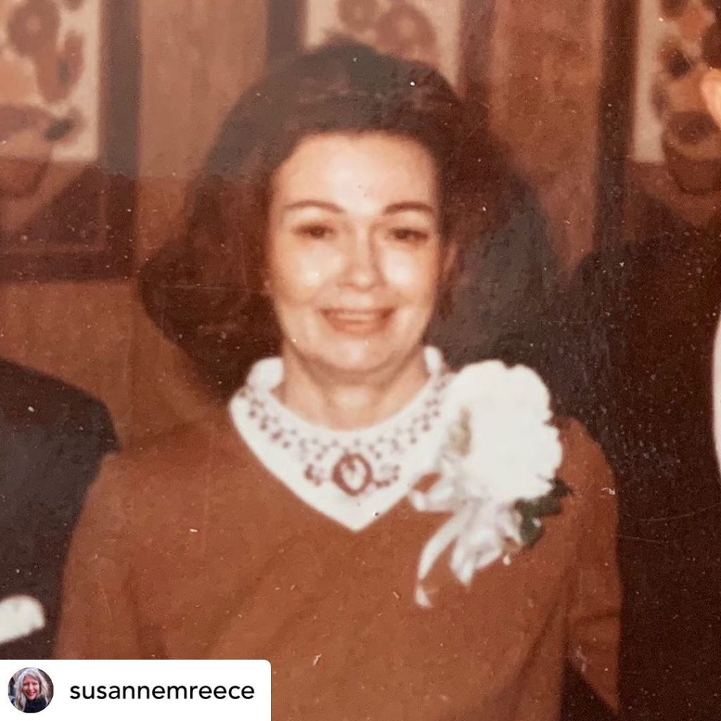 A brown tinted photograph of a white woman with dark hair wearing a shirt with a white patterned collar and a large white flower pinned to its right.