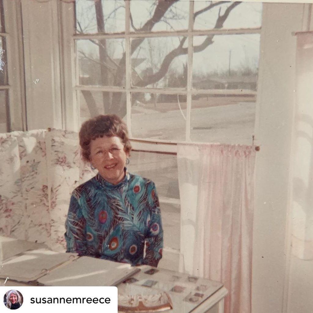 A smiling older white woman with short brown hair and a peacock feather patterned turtleneck sits at a table with an open binder in front of her. Behind her is a large window with low hanging patterned white curtains, showing a tree, houses and road outside.