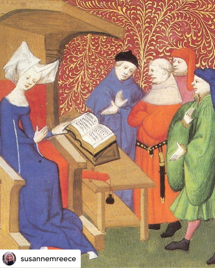 Five traditional European figures wearing blue, red and green, regarding a text, set against red wall with gold floral designs.