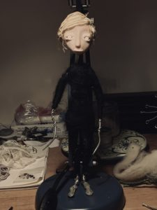 Pale puppet figure with black clothes and long metal wires for hands.