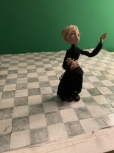Pale puppet figure in dark clothes kneeling on one knee, holding a golden jar in one hand, reaching up with the other hand.