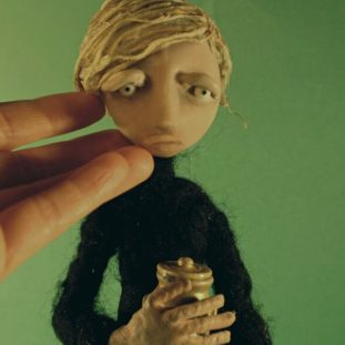 Hand touching the face of pale puppet figure wearing dark clothes, holding a gold jar.