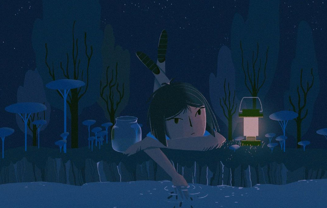 A girl lays on her stomach on the edge of a pond, looking in and running her fingers through the water