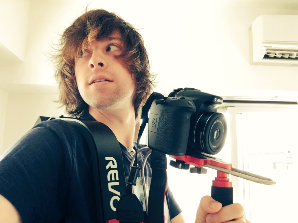 Jon Bero holds a camera while looking over his shoulder